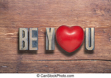 be you phrase combined on vintage varnished wooden surface with heart symbol inside