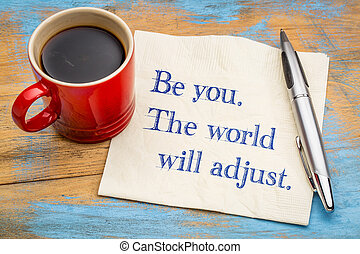 Be you. The world will adjust. Motivational handwriting on a napkin with a cup of coffee