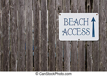 Beach access sign on wooden fence