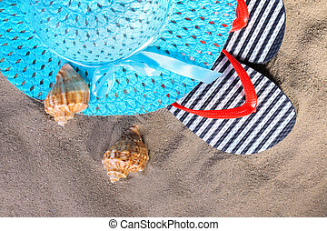 beach accessories. Flip-flops, a hat and seashells on the sand of the sea. Top view