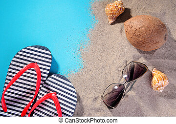 beach accessories. Flip flops, glasses from the sun, shells and coconut on the sand of the sea. on a blue background. Top view