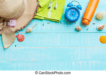 Beach accessories including sunglasses, sunscreen, hat beach, shell, alarm clock, green towel and Earphone on bright blue pastel wooden background for summer holiday and vacation concept.