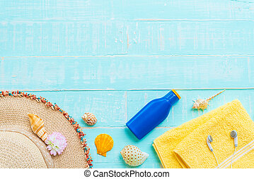 Beach accessories including sunglasses, sunscreen, hat beach, shell, yellow towel and Earphone on bright blue pastel wooden background for summer holiday and vacation concept.