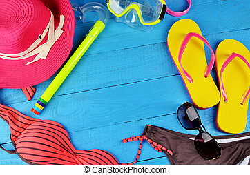 Beach accessories on blue wooden background