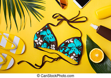 Beach accessories on yellow background.