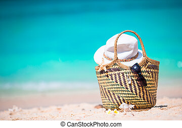 Beach accessories - straw bag, sunglasses, hat on the beach