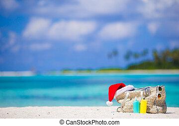 Beach accessories with Santa Hat on white tropical beach -...