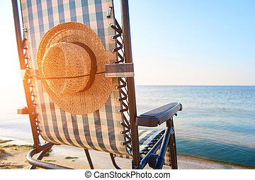 Beach accessories, woman's hat affixed to deck chair back....