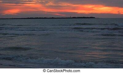 Beach after sunset with lighthouse far away - Beach after...