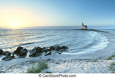 Beach and lighthouse in sunset colors