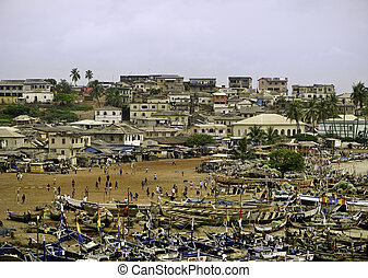 Very crowded beach with a market and numerous fishing boats in Accra in Ghana