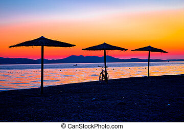 Beach and parasols on colorful sunset view