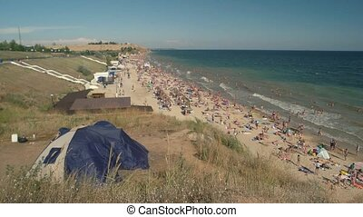Beach and people from distance. Blue sea and sky.