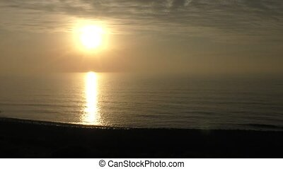 Beach and sinking sun - Wave beach and sinking sun in...