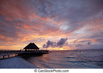 Beach and tropical houses on sunset