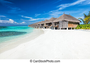 Beach and water villas on a small island resort in Maldives, Indian Ocean.