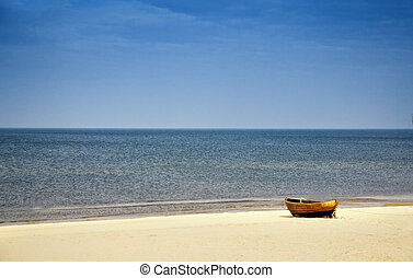 beach scene with wooden boat at baltic sea, north germany