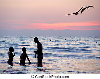 Beach at sunset - Family playing in the water at sunset