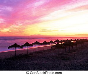 Parasols on beach at sunset, Torrox Costa, Costa Tropical, The Axarquia, Malaga Province, Andalucia, Spain, Western Europe.