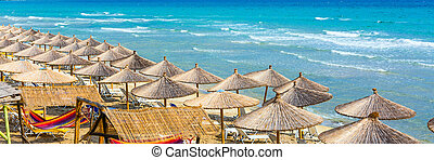 beach background with turquoise sea water waves and umbrellas, Greece