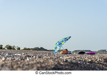 Beach bag and towels under sun umbrella on a beach