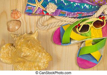 beach bag, flip flops, sunglasses, on wooden background. Top...