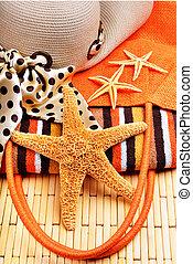 Beach bag, starfish, beach hat, towel on a wooden background