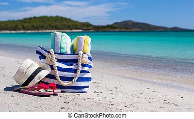 Beach bag, straw hat, flip flops and towel on white tropical beach