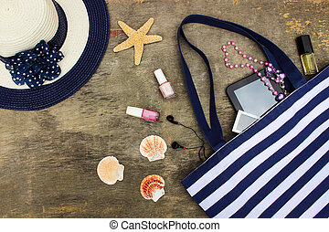 Beach bag, sun hat, cosmetics, mobile phone, tablet, seashells headphones and beads on old wooden background.