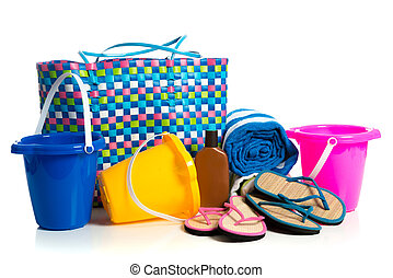 Beach bag with buckets, towel, flip-flops and suntan lotion on a white background