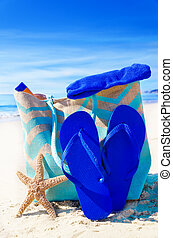 Beach bag with flip flops, starfish and towel by the ocean