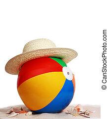 beach ball and hat on beach sand