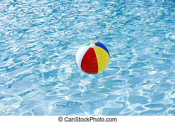 Beach ball floating on surface of swimming pool water