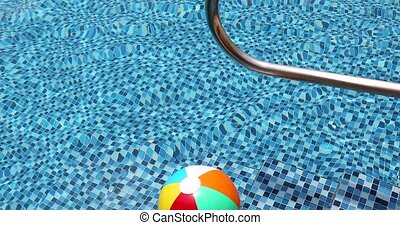 Colorful inflatable ball floating in swimming pool, summer vacation concept.