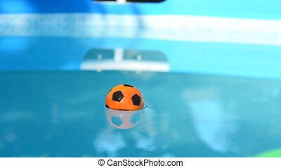 Children's Playing Beach Ball Floating on Water in Swimming Pool.