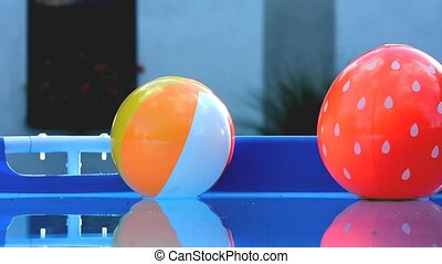 Beach balls in pool - Colorful beach balls floating in a...