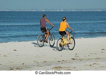 Beach Biking - People riding bikes on the beach, Fort Myers,...