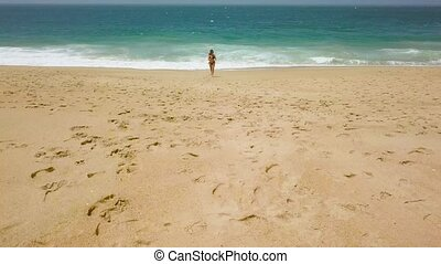 Beach bikini woman carefree running from the water on the beach. Picturesque ocean coast of Portugal