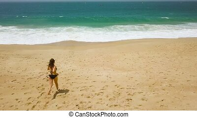Beach bikini woman carefree running to the water on the beach. Picturesque ocean coast of Portugal