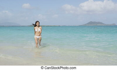 Beach bikini woman walking out of sea after swimming in the ocean on vacation travel getaway holidays. Beautiful young multiracial Asian Caucasian female model, 20s. RED EPIC SLOW MOTION, 96 FPS.