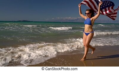 Beach bikini woman with US flag running along the water on the beach. Concept of Independence Day USA. Slow motion