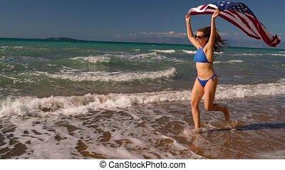 Beach bikini woman with US flag running along the water on...