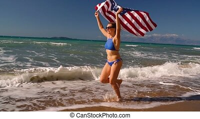 Beach bikini woman with US flag running along the water on...