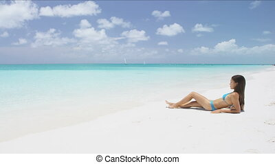 Beach body woman sun bathing on travel vacation. Sexy bikini body woman relaxing sun tanning lying down sunbathing on perfect paradise beach at tropical luxury destination in the Caribbean.