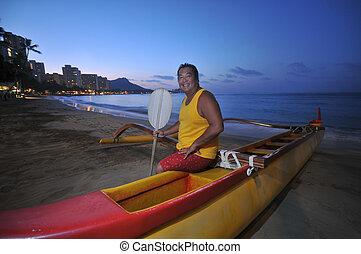 Beach boy in an outrigger canoe
