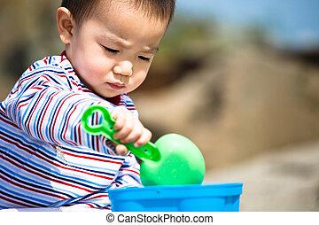 Beach boy - A cute asian boy playing with sand on the beach