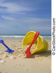 Beach bucket and spades. - Summer vacation. A childs yellow...