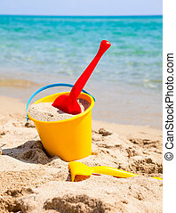 Beach bucket with spade - Yellow sand pail and shovel on a ...