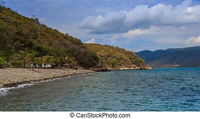beach by island village resort surf of azure sea on foreground