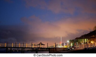 Beach cafe at night near the sea. Floodlights beautifully illuminate the clouds in the sky. People walk in the sand. TimeLapse